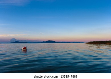 Lake Balaton with the Badacsony mountan in the background after sunset with a buoy