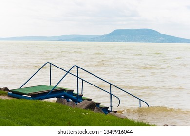 Lake Balaton with pier stairs with the Badacsony mountain in a rainy day in Hungary