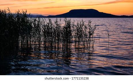 Lake Balaton at sunset with the sihouette of Badacsony hill