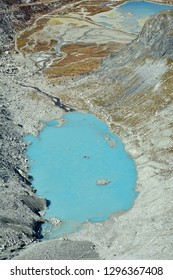 Lake at the base of a glacier, with a characteristic turquoise color. The melting glacier feeds the lake from the bottom and left of the image