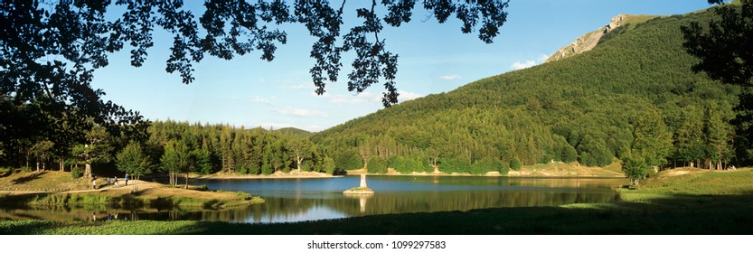 lake between green mountains and forests