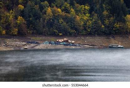 Lake Bicaz, fall season. Boats and small ships on Bicaz Artificial Lake. Autumn season with cloudy sky and foggy weather, Carpathian Mountains.