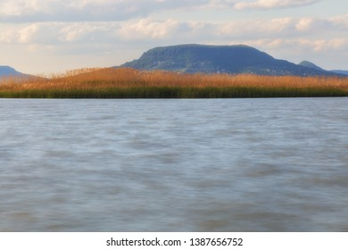 Lake Blaton on a cloudy day with island full of reed and Badacsony mountains in the background