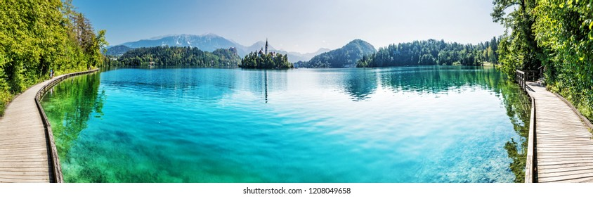 Lake Bled with castle and Assumption of Mary Pilgrimage Church, Slovenia, Europe. Travel destination. Mountains, architecture and reflections in water. Panoramic photo.