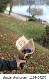 Lake Bled, Slovenia - October 29, 2018: Hand holding a pack of roasted chestnuts wrapped in newspapers. Unrecognizable person enjoying nature and food at Lake Bled, Slovenia.