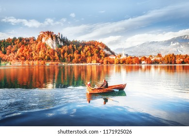 Lake Bled in Slovenia. Romantic couple paddling wooden boat at the background of captivating seasonal autumn landscape, forest with yellow leaves and old castle on hill. Famous and popular landmark.