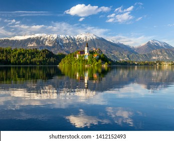Lake Bled, Slovenia. Sunset, warm light on Assumtion of Mary church on island in center of the lake Tranquil scene with snow covered mountains in background.