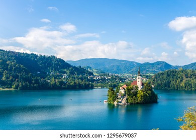 Lake Bled with St. Marys Church of Assumption on small island. Bled, Slovenia, Europe. Mountains and valley on background. Areal view from above. Staircase, stairs lead to church. Space for your text.