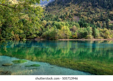 Lake with blue, transparent water, autumn forest and it's reflection, China