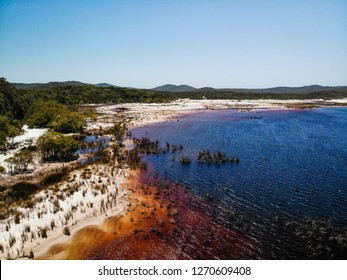 Lake Boomanjin on Fraser Island on a sunny day.  The lake is red from the tea tree oil