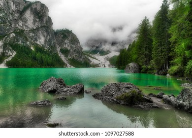 Lake of Braies in a cloudy summer day with forest around and fog in the background, Dolomites - Italy