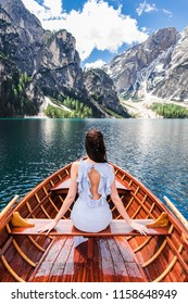Lake Braies, Italy. A girl in a dress sits in a boat. Enjoys beautiful mountain views