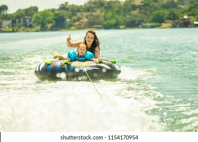 LAKE BUCHANAN, TEXAS - CIRCA JUNE 2018: A mother and daughter ride a water tube while being pulled by a motorboat. They wear a life jacket and jumps over the wake created by the boat.
