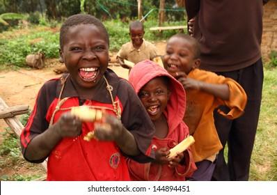 LAKE BUNYONI, UGANDA - CIRCA SEPTEMBER 2012.  A group of unidentified Ugandan children smile while enjoying eating sugarcane near Lake Bunyoni, Uganda during September 2012.