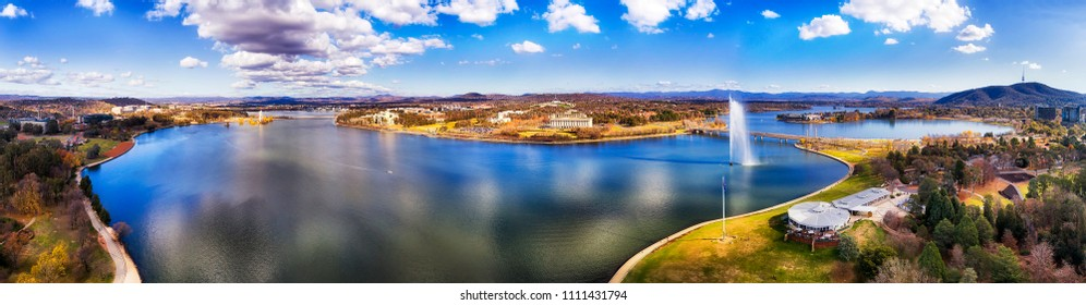 Lake Burley Griffin in the middle of Canberra city on a sunny day elevated over shores with capitol hill and government district between surrounding hill ranges.