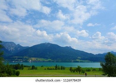Lake called Wolfgangsee in Austria with mountains in the background and clouds on the sky and grass in the front, Europe