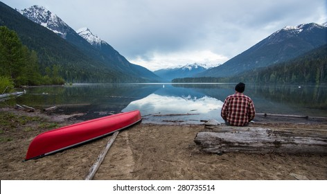 Lake with a canoe and man looking while sitting on a log
