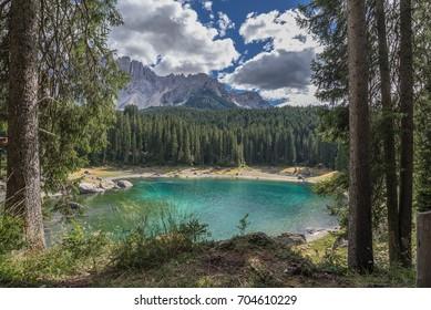 Lake of Carezza, a small alpine lake located in Ega valley, beneath the slopes of Latemar mountain massif in background, Nova Levante municipality, Dolomites, Trentino, Alto Adige, South Tyrol, Italy