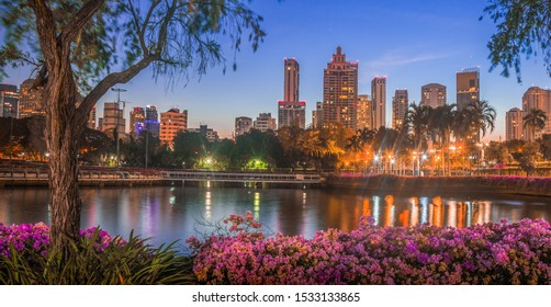 Lake in City Park under Skyscrapers at Night. Benjakiti Park in Bangkok, Thailand