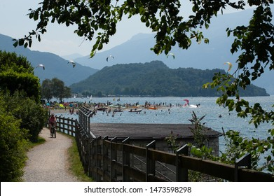Lake Como, Italy - July 21, 2019. Summer activities on a beach in mountain lake - cycling, windsurfing, swimming, boating, kitesurfing. Girl riding bike on bicycle path. Alp mountains on background