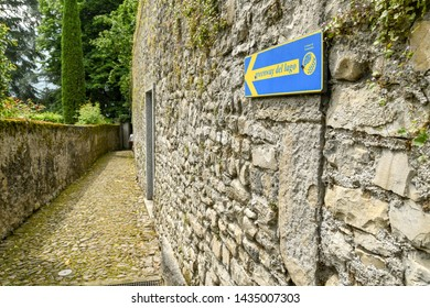 LAKE COMO, ITALY - JUNE 2019: Sign showing walkers the route on a walking trail on Lake Como - the Greenway del Lago di Como.