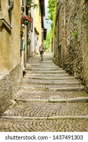 LAKE COMO, ITALY - JUNE 2019: Person walking up a narrrow lane with cobbled steps on the route of the Greenway del Lago di Como, which runs around part of Lake Como.