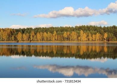 Lake in a delightful autumn forest at sunny day. Autumn trees with reflection. Unusual and picturesque scene. Beauty world. Russia.