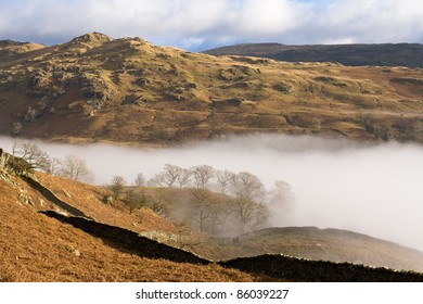 lake district landscape view sunny peaks as morning mist moves up the valley