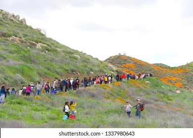 Lake Elsinore, CA - March 09, 2019: Thousands of people line the trails to view the orange explosion of wild poppy flowers along Walker Canyon in So California. Many people going off marked trails.