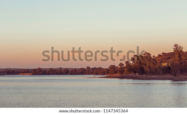 Lake with eucalyptus forest in the background at sunset, with clear sky and orange on the horizon, Spain