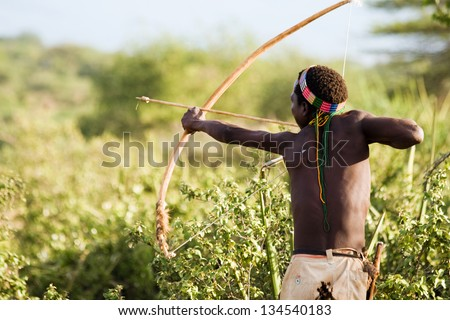 LAKE EYASI, TANZANIA - FEBRUARY 18: An unidentified Hadzabe bushman with bow and arrow during hunting on February 18, 2013 in Tanzania. Hadzabe tribe threatened by extinction.