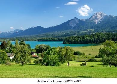 Lake Faak under mountain chain of Karawanken Alps, Austria