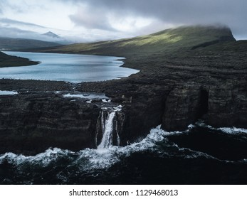 A lake flowing via a waterfall over cliffs in the rough sea with green mountains and hills in the background and the sea and cliffs in the foreground during a foggy day on the Faroe Islands