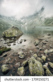 Lake in foggy mountains in the High Tatras. Slovakia. Central Europe. Scenic landscape of a crystal clear lake against the background of mountains in the fog.
