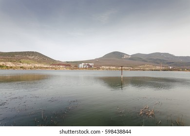 A lake in the foothills of the mountain of the city. The abandoned factory of the times of the Cold War of the USSR. Today, the location of the bike show