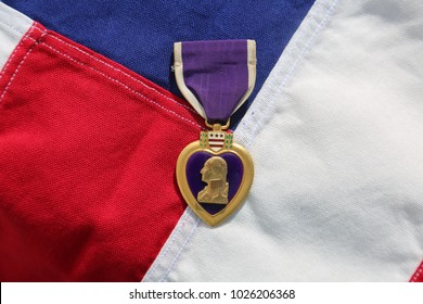 Lake Forest CA - 2/14/2018: World War Two Purple Heart lays upon an American Flag. Purple Hearts are awarded to Military who are wounded, killed, or shown extreme bravery and valor in battle.