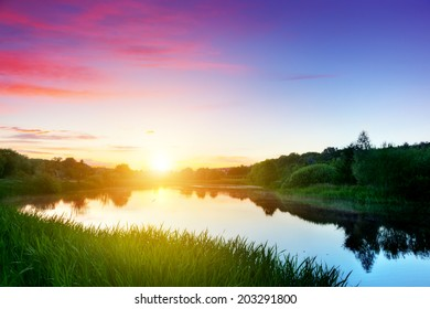 Lake in forest at sunset. Peaceful and calm mood. Romantic sky with red clouds
