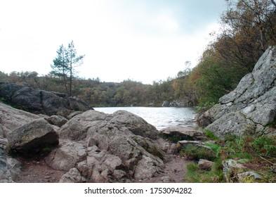 Ein See im Wald, umgeben von Felsen