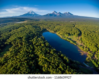 Lake in forest and volcano mountainscape at horizon aerial