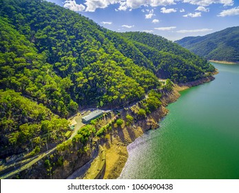 Lake and forested hills under white fluffy clouds on bright summer day
