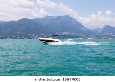 Lake Garda, Italy - August 3rd 2018:Lake Garda - A luxury speedboat races along the lake in front of beautiful mountains. Spray from its wake.  The speed boat is driven by German tourists.