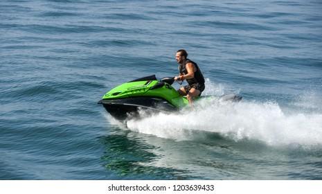 LAKE GARDA, ITALY - SEPTEMBER 2018: Person riding a fast jet ski skimming the surface of Lake Garda.
