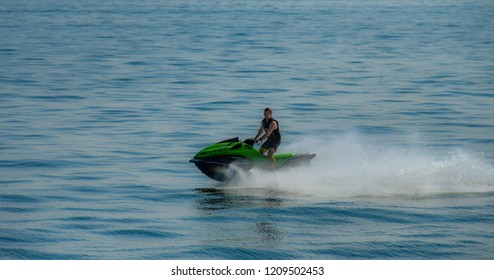 LAKE GARDA, ITALY - SEPTEMBER 2018: Person riding a fast jet ski skimming the surface of Lake Garda.