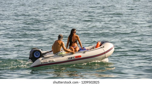 LAKE GARDA, ITALY - SEPTEMBER 2018:  People in a small inflatable dinghy with outbroad motor cruising slowly past the harbour in the town of Garda on Lake Garda.