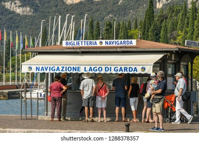 LAKE GARDA, ITALY - SEPTEMBER 2018: People queuing at the ticket kiosk for ferries from the town of Garda on Lake Garda.