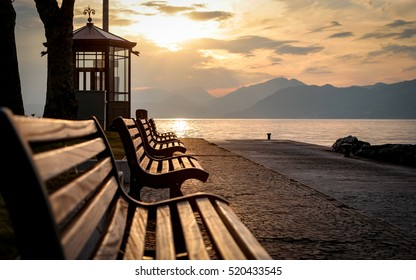 Lake Garda, Italy. A tranquil sunset view of benches looking over Lake Garda, Italy, towards the Italian Alps.