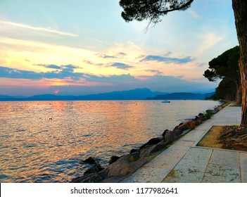 Lake Garda seen from the coast, where there is a tree-lined avenue. It's the sunset and the sky is a bit cloudy.
