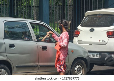 Lake Gardens, Kolkata, 5/5/2020: A car driver donating money (10 rupees currency note) to a poor Indian street-girl at a traffic signal near Rabindra Sarobar Lake. The girl is seen wearing face mask.