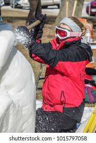 LAKE GENEVA, WI/USA - FEBRUARY 1, 2018: A sculptor wearing goggles slices into a large block of snow early in the U.S. National Snow Sculpting Competition during a winter festival here.