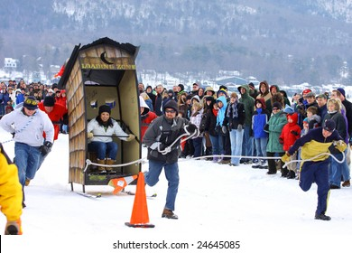 LAKE GEORGE, NY - February 7, 2009: An outhouse race team runs their hardest to win at the February 7 , 2009 Lake George Winter Carnival.